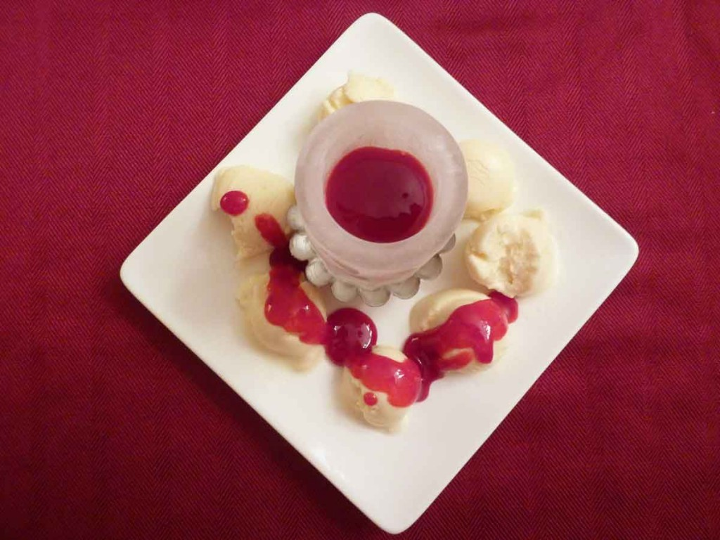 Ice cream balls and ice shot glass with raspberry coulis
